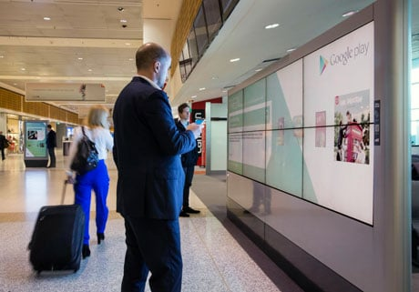 A traveller interacts with a Google NFC ad at Sydney airport