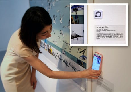 A visitor uses NFC to get information about an exhibit at the Savina Museum of Contemporary Art