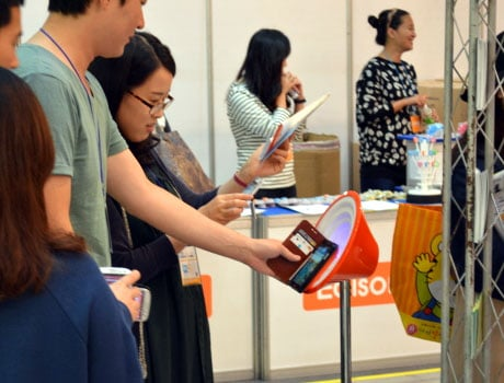Exhibition visitors try out SK Planet's colourful NFC touchpoints