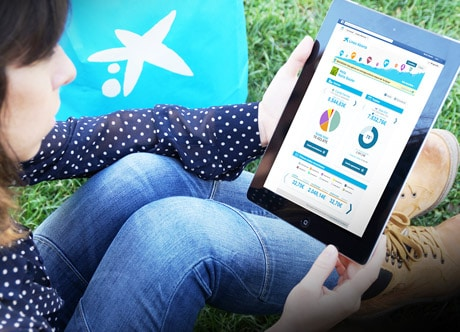Person holding iPad showing Caixa Facebook banking app
