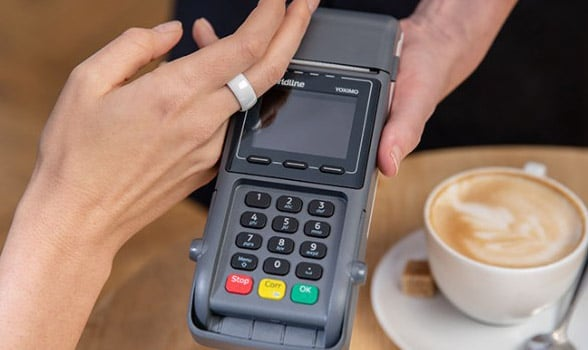 A person makes a contactless payment with an NFC ring