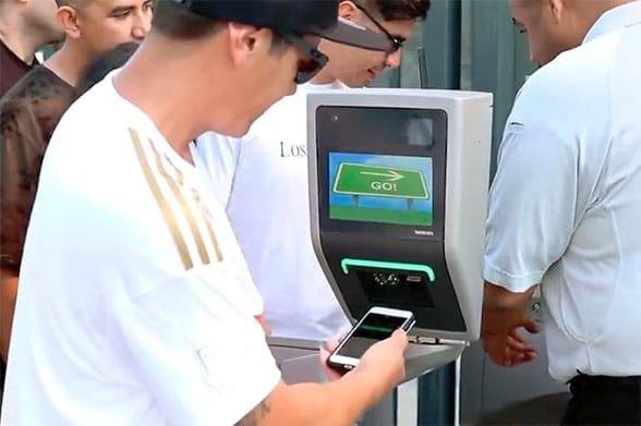 Fans use their iPhones and Apple Watches at a contactless turnstile to get in to an LAFC match