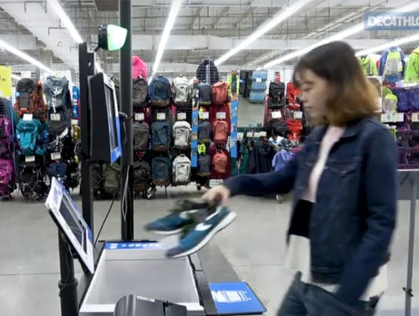 Woman scans trainers at self-checkout