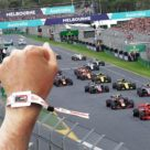 Hand with tappit wristband and F1 race track and cars