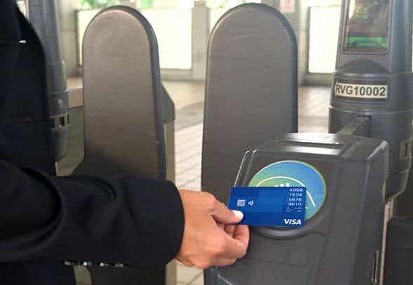 A passenger pays for a fare with a contactless card at a Metrorail ticket barrier