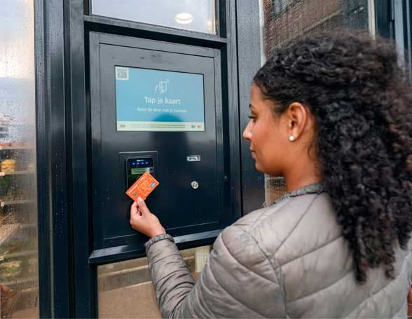 Woman tapping bank card on screen on wall