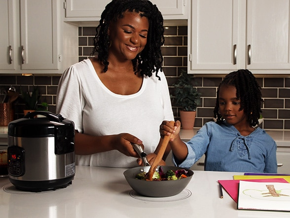 A mother and daughter cooking with Ki Cordless Kitchen appliances