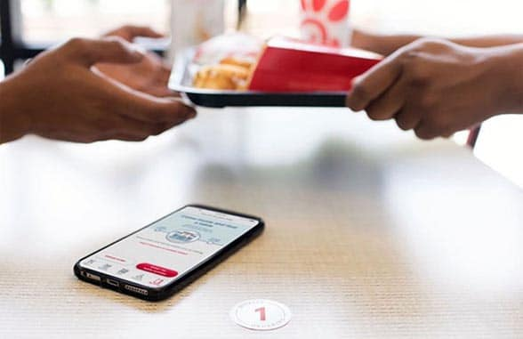 Smartphone on table with fast food