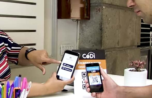 2 smartphones held in hands being used to make qr payment