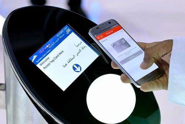 A person using an NFC phone as a virtual Nol card