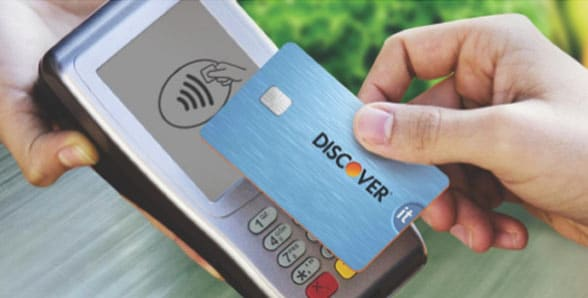 Contactless Discover It card being tapped on payment terminal