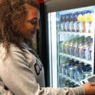 Woman using nfc phone to buy item from vending machine