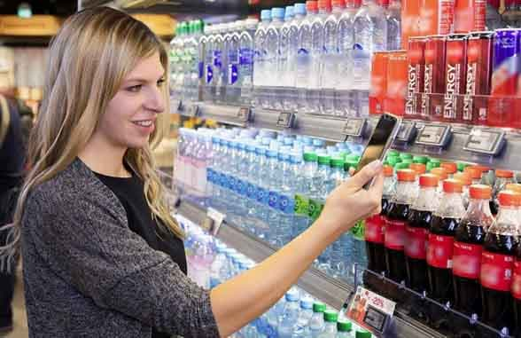 Woman using smartphone to scan SES-imagotag digital shelf labels at Munich Airport