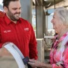 Man smiling at woman as she uses Transport Canberra MyWay transport ticketing card