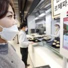 Woman wearing mask using LG CNS biometric payment POS