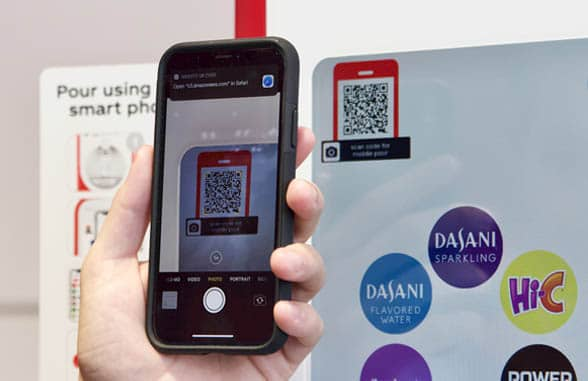 Coca-Cola Freestyle contactless drinks dispenser showing phone with qr code