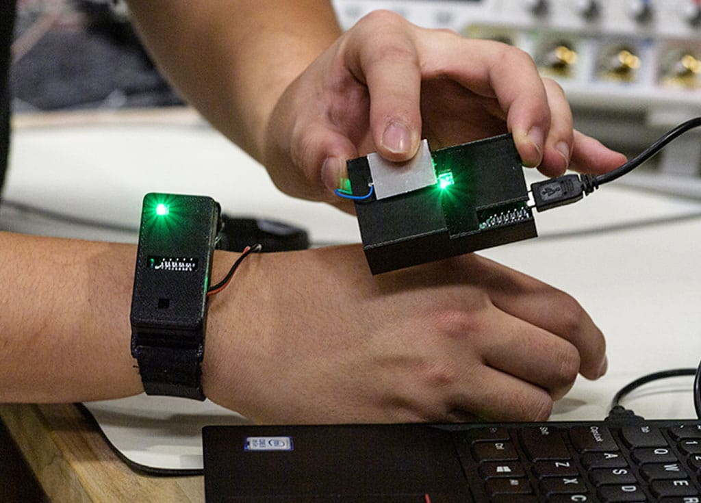 Prototype wearable showing smartwatch transferring data to laptop