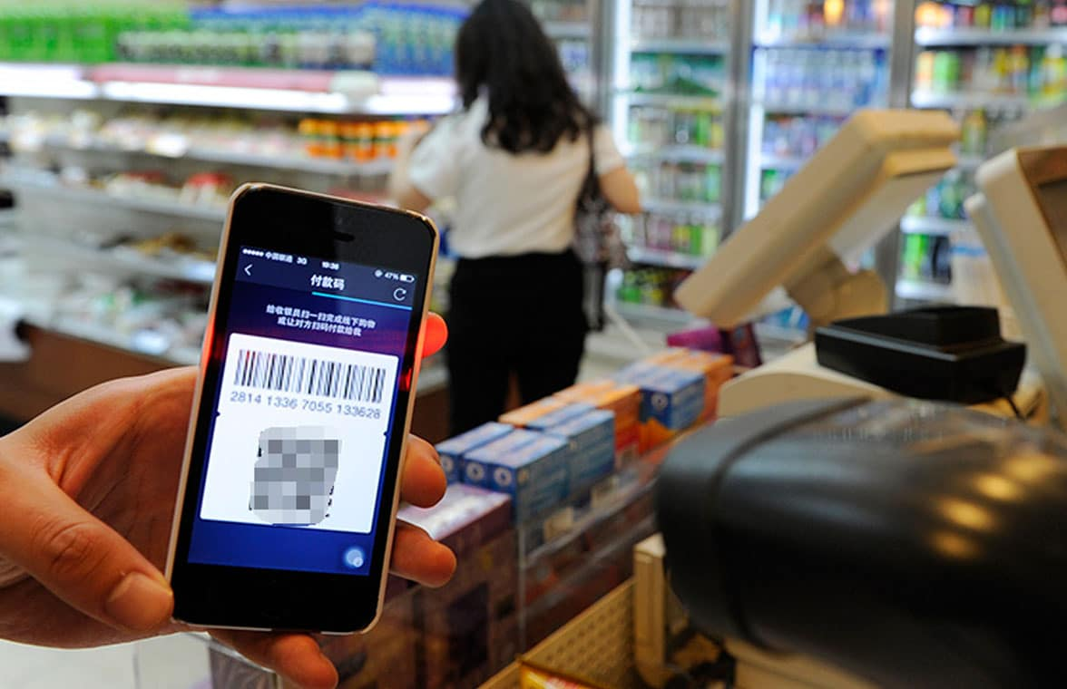 Chinese consumer using smartphone to make QR mobile payment