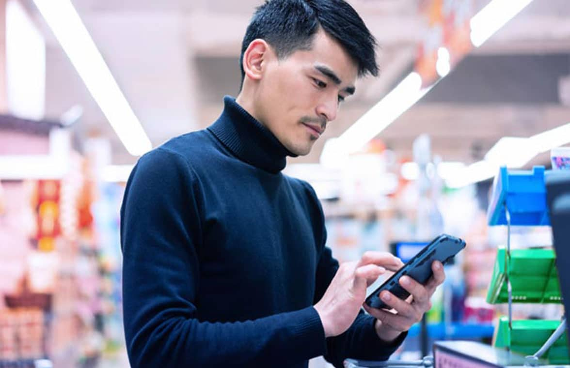 Man using smartphone to make payment using mobile wallet in store