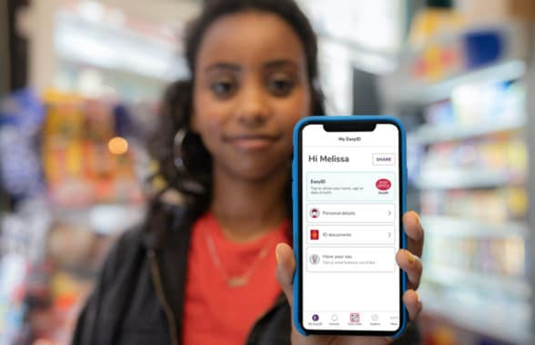 Woman holding phone with Post Office digital ID EasyID app
