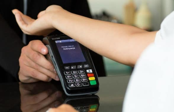 Walletmore NFC implant being used by consumer to make a contactless payment with their hand